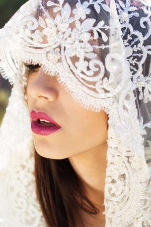 women subtle: Face of a beautiful bride hidden by white veil