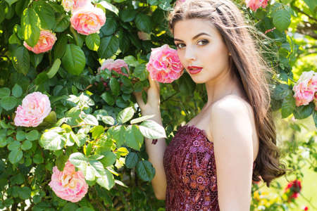 Beautiful young woman with fashion makeup posing near pink roses in a garden Standard-Bild
