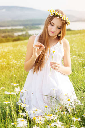 Cute child girl is lying at  green camomile field with mountains view photo