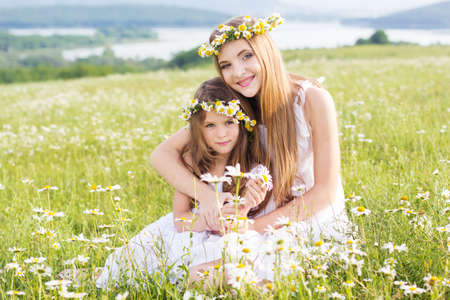 Cute child girls is lying at  green camomile field with mountains view photo