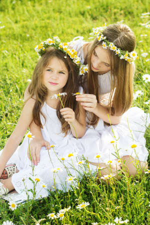 Cute sisters girls is playing at  green camomile field photo