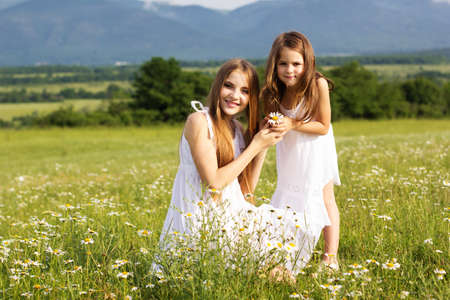 Cute sisters girls are wearing white dresses at  green camomile field with mountains view photo