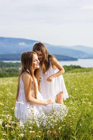 weisse kleider: Nette Schwestern M�dchen tragen wei�e Kleider spielen auf gr�nem Kamillenfeld mit Blick auf Berge