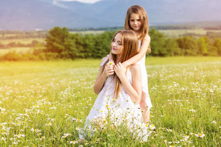 Cute sisters girls are wearing white dresses at  green camomile field with mountains view, sunset time photo