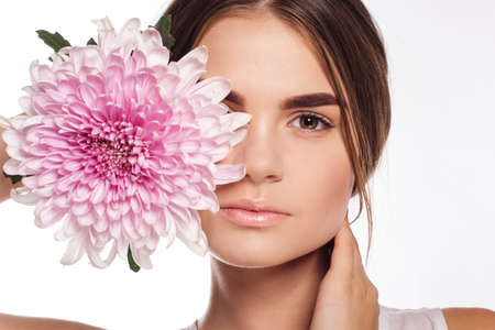 Portrait of pretty young teen girl with perfect nude makeup with pink chrysanthemum flower