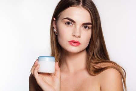 modelos desnudas: Retrato de la muchacha atractiva caucásicos con la piel perfecta aislados en blanco en el estudio es la celebración de crema de piel de la cara Foto de archivo