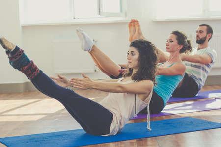 Mladí sportovní trio skupina chlapec a dvě dívky praktikují cvičení jógy ve studiu