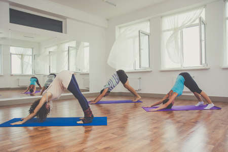 people human mind: Young sportive trio group boy and two girls are practicing yoga exercises in the studio