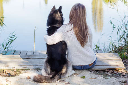 happy teenager: Back view of girl and her blueyed dog husky is sitting outdoors near lake, autumn time Stock Photo