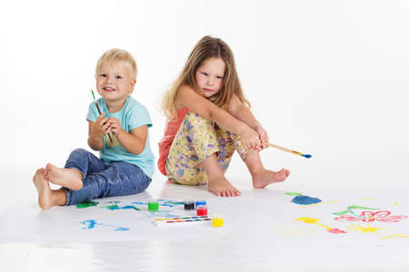 aquarelle painting art: Two pretty children are drawing pictures by paints