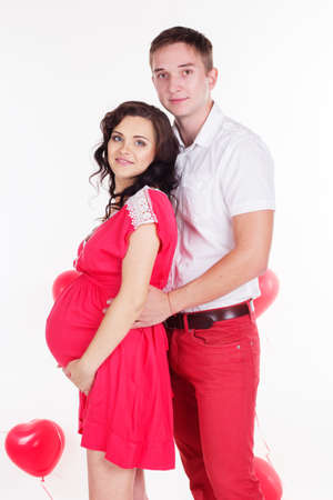 pregnant woman with husband: Young attractive couple: pregnant girl and happy man are wearing red clothes with red heart shape balloons isolated on white Stock Photo