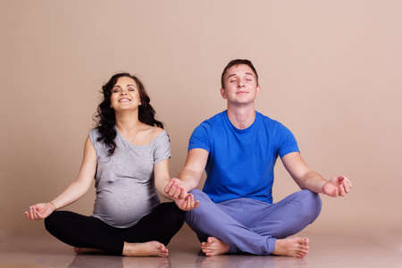 Young attractive couple: pregnant woman and man are doing yoga exercise together in studio