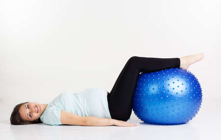 Caucasian young woman exercising yoga for pregnant with blue fitball in studio isolated on white background