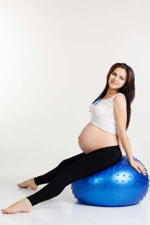 Caucasian pretty woman exercising stretching and yoga for pregnant with blue fitball in studio isolated on white background