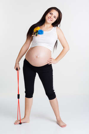 belly band: Pregnant woman doing stratching exercises with resistance bands tube isolated on white in studio