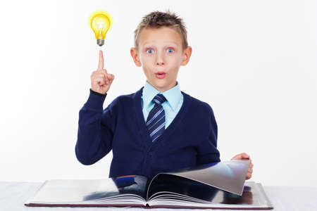 preschool: Cute little surprised preschooler boy with a raised finger and bulb is wearing official clothes, isolated over white background Stock Photo