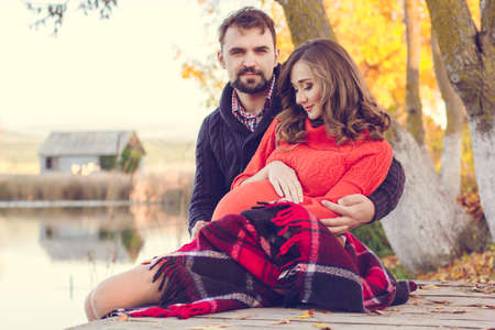 picnic park: Happy couple pregnant woman and man are sitting in warm clothes and wrapped in blanket infront lake view Stock Photo