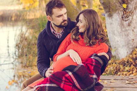 husband and wife: Happy couple pregnant woman and man are sitting in warm clothes and wrapped in blanket near the lake Stock Photo