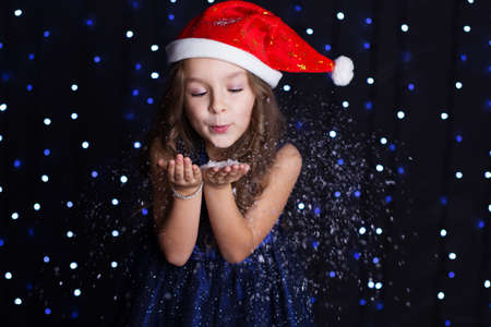 artificial lights: Happy child girl is blowing white artificial snow in hands in a studio background scene with lights for a holiday concept.