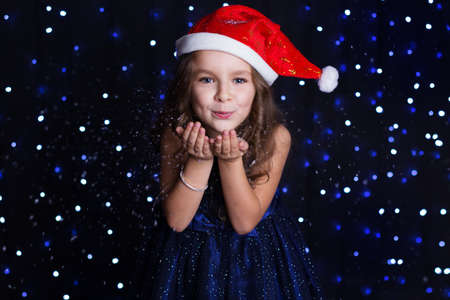 artificial lights: Happy child girl is with white artificial snow in hands in a studio background scene with lights for a holiday concept.