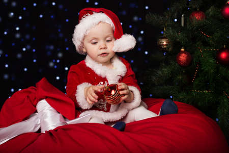 christmas costume: Happy little baby is holding christmas ball. New Years holidays. Baby in a red Christmas costume with gift