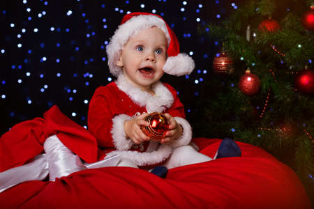 costume ball: Happy little baby is sitting near fir-tree and holding christmas ball. New Years holidays. Baby in a red Christmas costume with gift