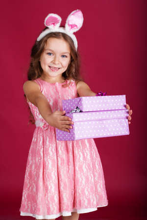 Cute little happy girl is wearing pink dress and bunny ears on red background is holding gift boxes