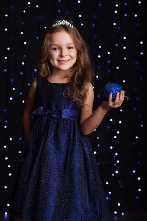 christmas crown: Feliz ni�a bonita ni�o est� usando vestido de la manera y la corona que sostiene la bola azul del �rbol de navidad en las manos m�s de fondo de escena con las luces, el concepto de vacaciones