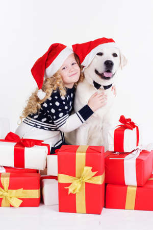 labrador christmas: Child blonde girl with labrador dog are wearing christmas hats. Happy child. Studio shot