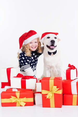 labrador christmas: Pretty blonde girl with white labrador dog are wearing christmas hats isolates on white Stock Photo