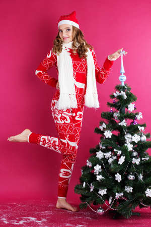 one girl: Pretty girl with funny grimace is wearing warm red pajamas and scarf isolated on red background
