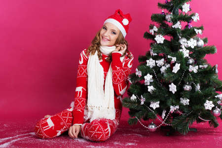 children hands: Pretty girl with funny grimace is wearing warm red pajamas and white scarf isolated on red background