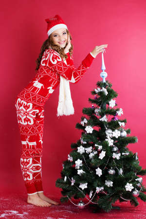 sweater girl: Pretty girl with funny grimace is wearing warm red pajamas and scarf near christmas tree Stock Photo