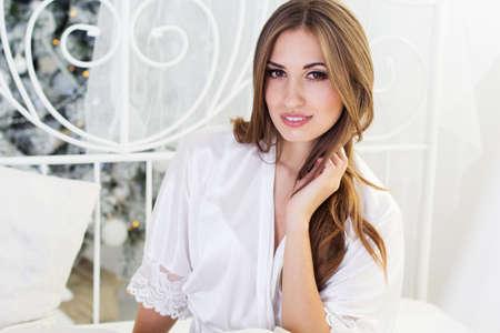 fille sexy: fille heureuse dans son lit blanc est en pyjama apr�s r�veiller pr�s de l'arbre de No�l