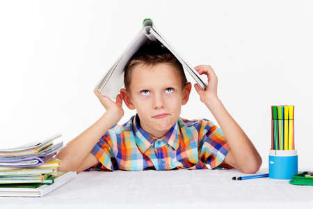Cute little serious sad boy is holding book on his head, isolated over white background