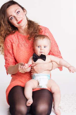 nene y nena: Hermosa madre con adorable peque�o hijo, la madre y el ni�o interior aislado en el fondo blanco, concepto de la felicidad