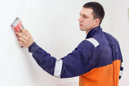 emery paper: Handyman is doing repair works with sandpaper on a white wall