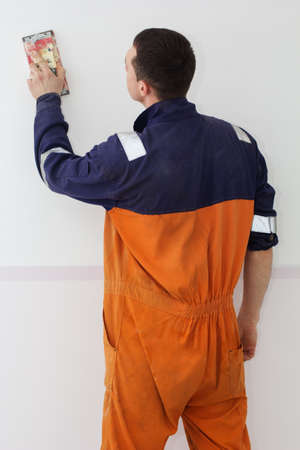 grind: Handyman is doing grind works with sandpaper on a white wall Stock Photo