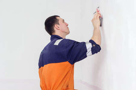 plasterwork: Handyman is doing grinding works with sandpaper on a white wall in room