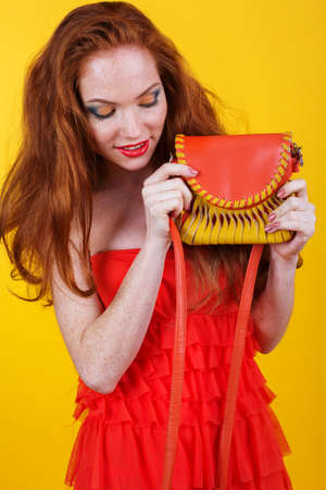 redheaded: Portrait of beautiful redheaded girl with fashion colorful makeup is holding orange purse Stock Photo