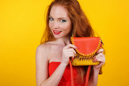 redheaded: Portrait of beautiful redheaded girl with fashion colorful makeup is holding orange fashion purse Stock Photo