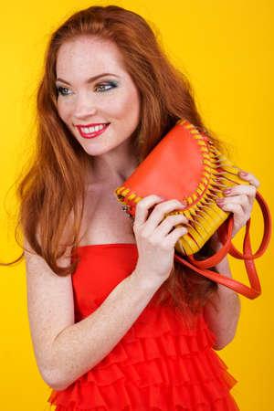 redheaded: Portrait of beautiful redheaded girl with fashion colorful makeup is holding orange fashion handbag