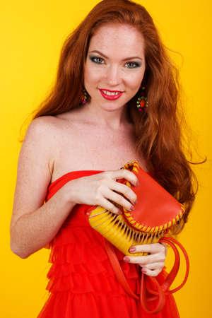 redheaded: Portrait of beautiful redheaded girl is holding orange fashion handbag