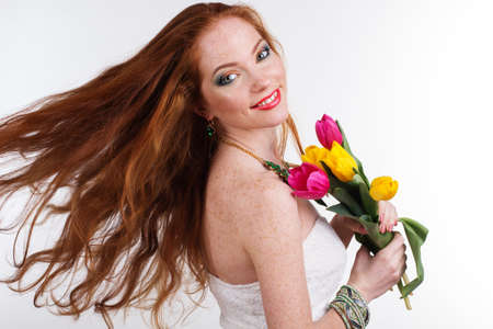 flying hair: Beautiful smiling girl with colorful tulips and flying hair, womans day