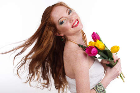 womans: Beautiful smiling girl with colorful tulips and flying red hair, womans day, spring time