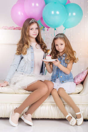 pink balloons: Two pretty girls sisters are celebrating birthday in a studio with cake and blue and pink balloons