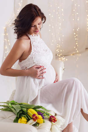 Beautiful pregnant woman with colorful tulips waiting a baby
