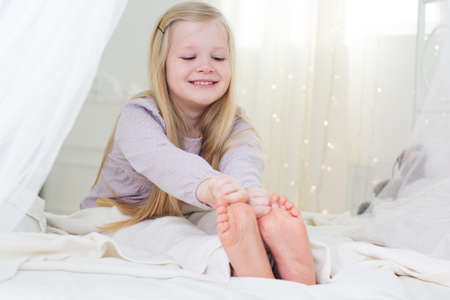 teen girls feet: Happy blonde child girl is holding her foots in the bed