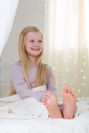 pajamas: Happy blonde girl is sitting barefoot in the bed
