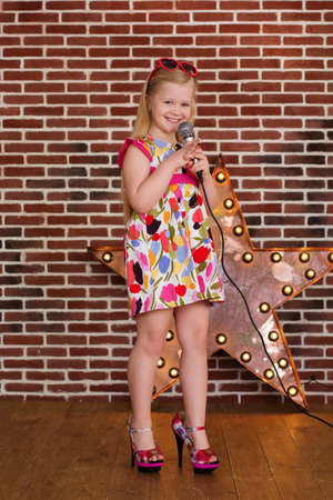 Beautiful little girl in dress and MOTHERS HEELS with microphone on brick wall background Reklamní fotografie